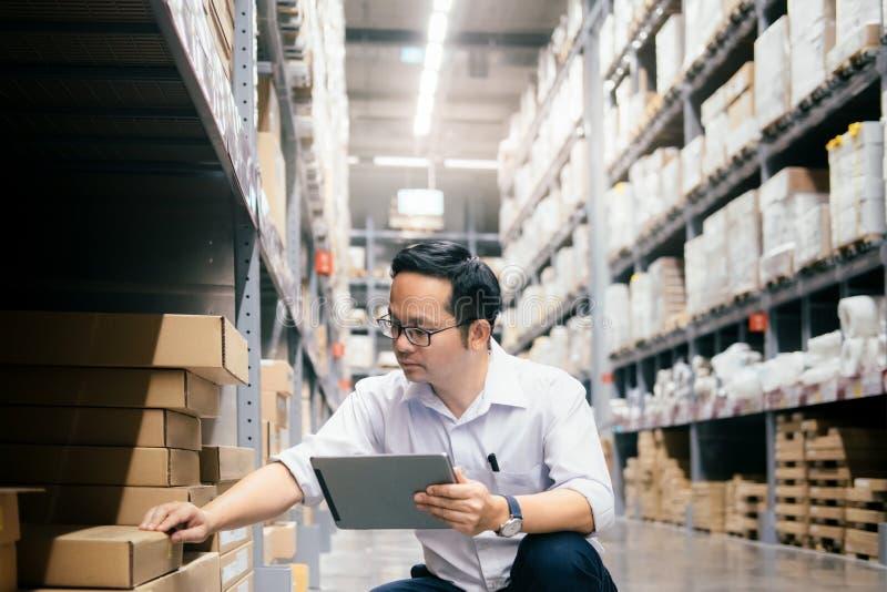 Trabalhador do armazém do homem que verifica bens no armazém imagens de stock