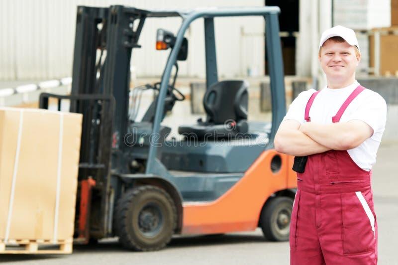 Trabalhador do armazém na frente do forklift fotografia de stock royalty free