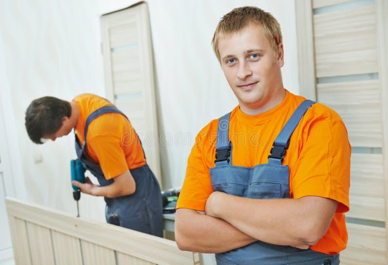 Trabalhador do carpinteiro da instalação da porta foto de stock royalty free