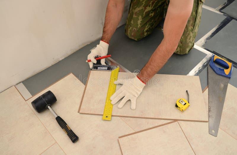 Trabalhador do carpinteiro que instala a placa de madeira do parquet durante a pavimentação de w imagens de stock royalty free