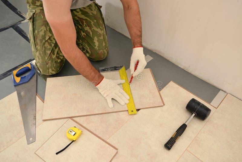 Trabalhador do carpinteiro que instala a placa de madeira do parquet durante a pavimentação de w fotos de stock