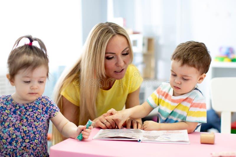 Trabalhador do centro de dia com as crianças que leem um livro no jardim de infância fotos de stock