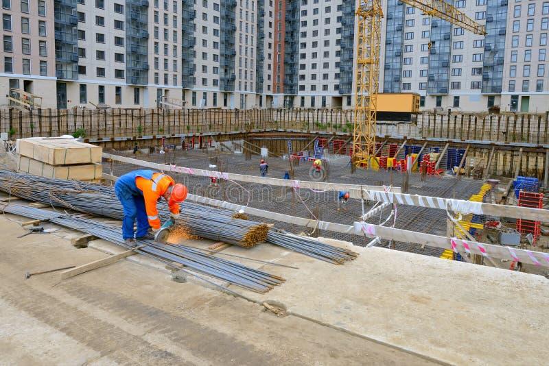 Trabalhador do construtor com as peças de metal do corte de máquina do moedor no const foto de stock