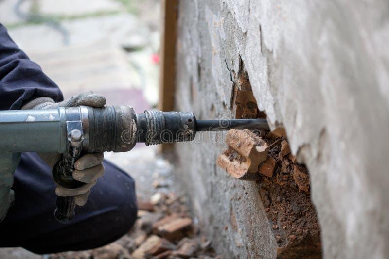Trabalhador do construtor com o equipamento da broca de martelo pneumático que quebra o Br imagens de stock