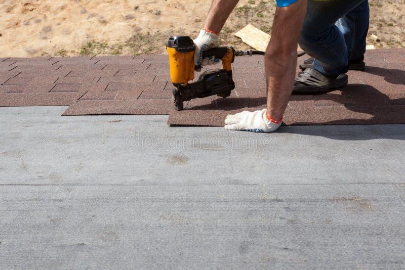 Trabalhador do construtor do Roofer com o nailgun que instala Asphalt Shingles ou telhas do betume em uma casa nova sob a constru imagens de stock