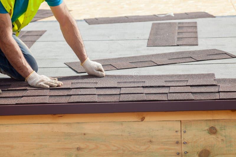 Trabalhador do construtor do Roofer que instala Asphalt Shingles ou telhas do betume em uma casa nova sob a construção imagens de stock royalty free