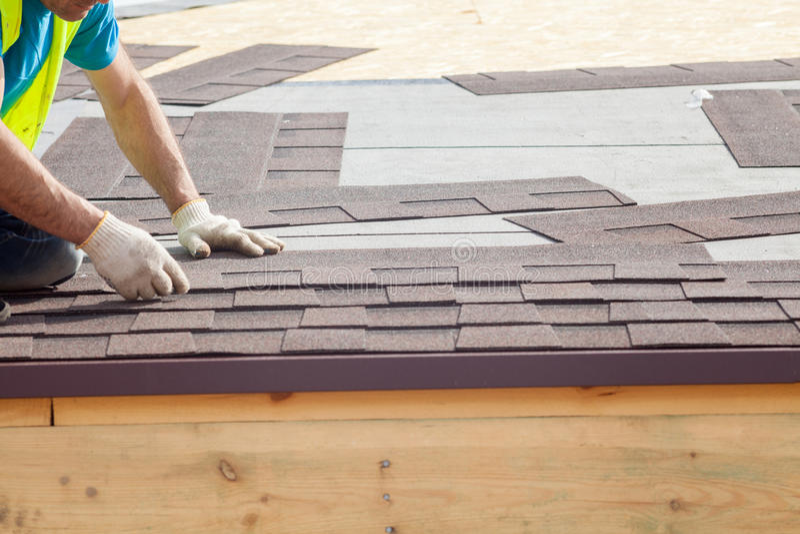 Trabalhador do construtor do Roofer que instala Asphalt Shingles ou telhas do betume em uma casa nova sob a construção fotos de stock