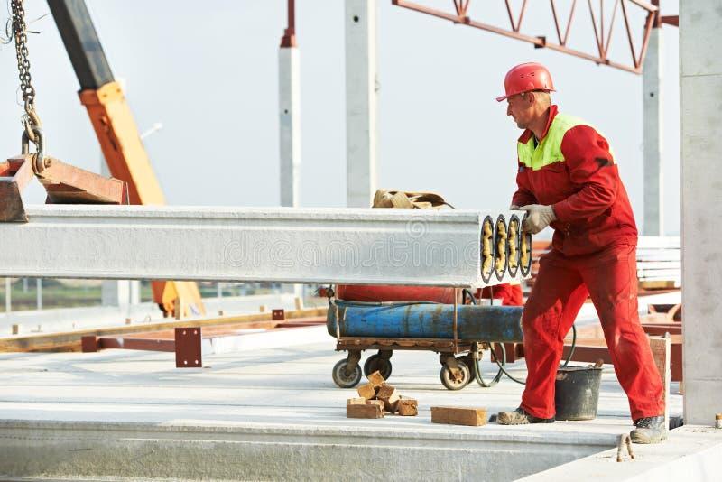 Trabalhador do construtor que instala a laje de cimento imagem de stock