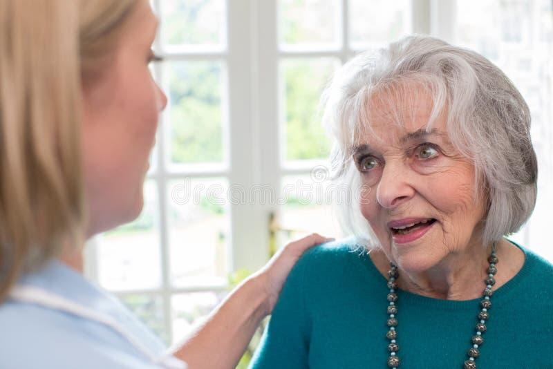 Trabalhador do cuidado que fala à mulher superior em casa foto de stock royalty free