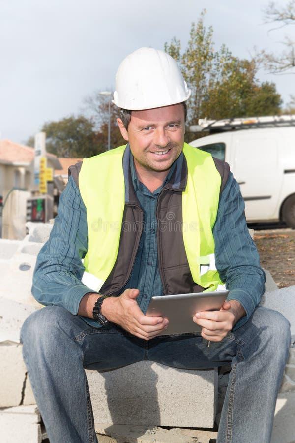 Trabalhador do homem da construção que olha na almofada do tablet pc ao sentar-se imagens de stock