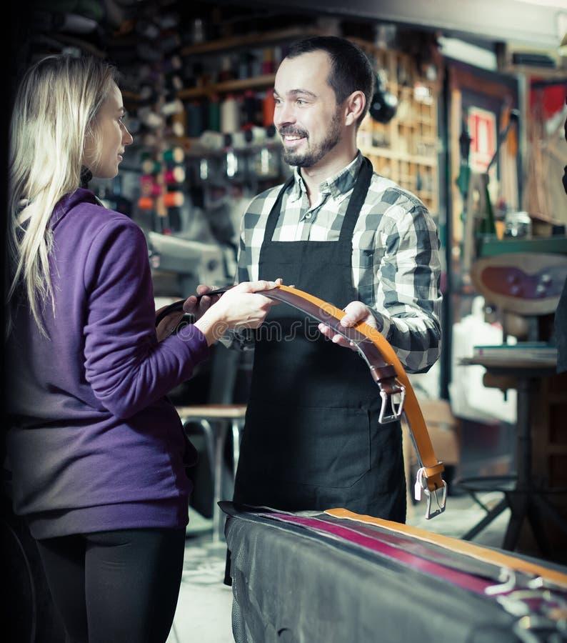 Trabalhador do homem novo que ajuda ao cliente fêmea em escolher a correia fotografia de stock royalty free