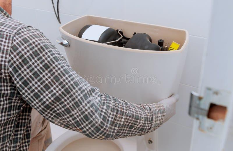 Trabalhador do homem que repara com o tanque do toalete no banheiro, close up imagens de stock