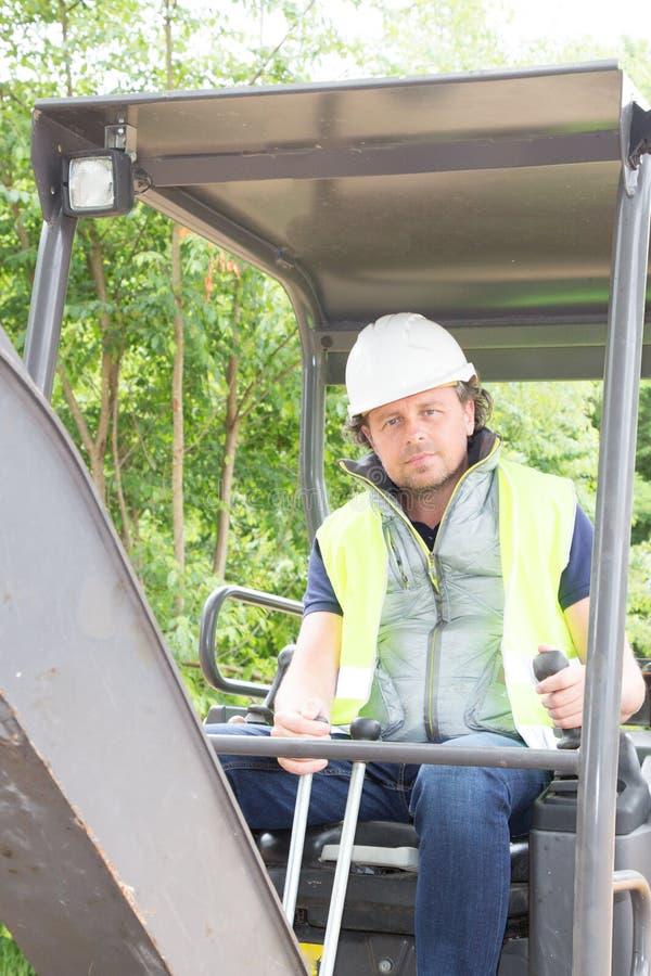 trabalhador do homem que usa o escavador no canteiro de obras imagem de stock
