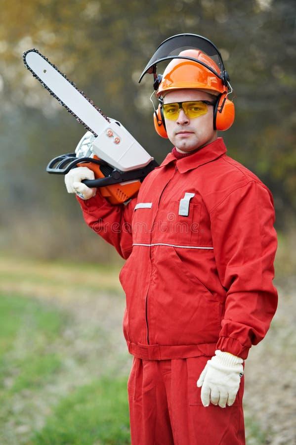 Trabalhador do lenhador com serra de cadeia dentro fotos de stock royalty free