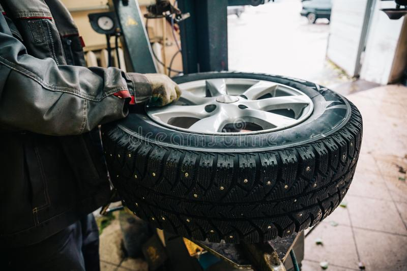 Trabalhador do mecânico de carro que faz a substituição e a roda do pneu que equilibram com equipamento especial na estação do se imagens de stock