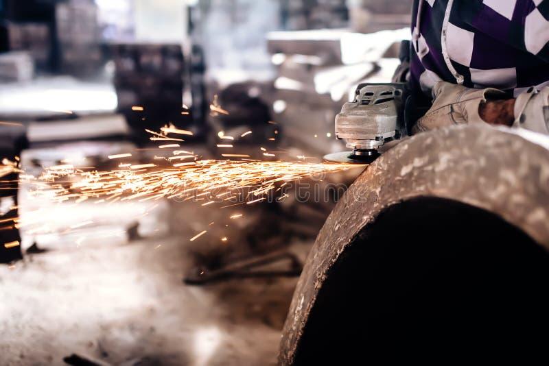 Trabalhador do mecânico que usa o moedor para lustrar um bloco do ferro fotografia de stock