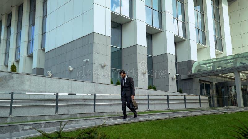 Trabalhador do mulato que deixa o centro do escritório após a neutralização profissional longa do dia de trabalho imagem de stock