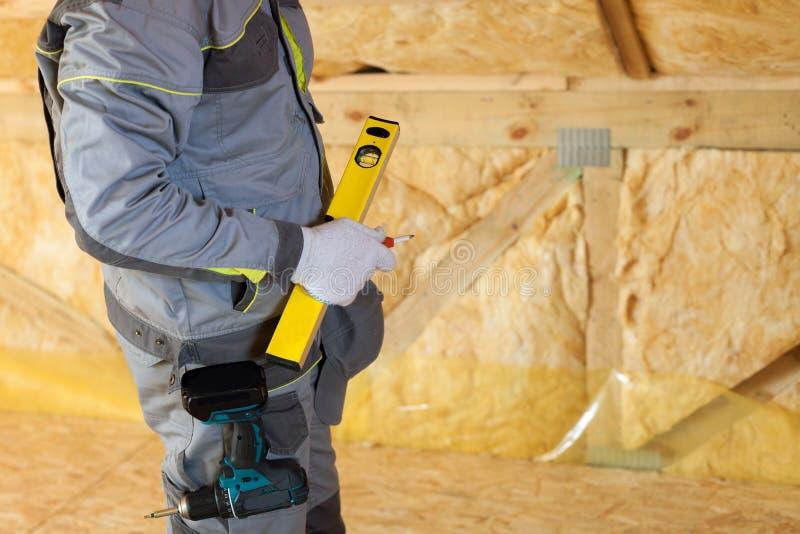 Trabalhador do pedreiro da construção com nível da construção e chave de fenda no sótão com a favor do meio ambiente fotos de stock royalty free