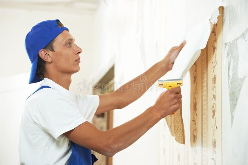 Trabalhador do pintor que descasca fora o papel de parede imagem de stock