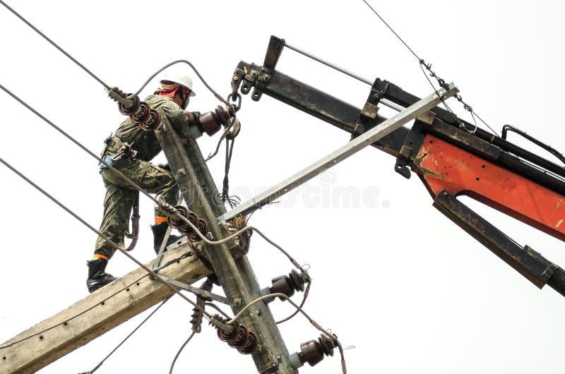 Trabalhador do reparador do lineman do eletricista no trabalho de escalada imagens de stock royalty free