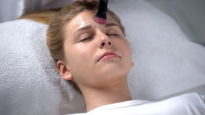 Trabalhador do salão de beleza que põe a máscara hidratando sobre a cara da menina, feminilidade imagem de stock