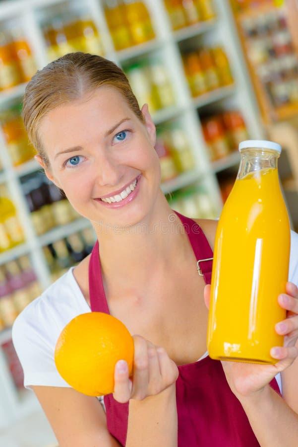 Trabalhador do supermercado que guarda o suco de laranja da garrafa foto de stock royalty free
