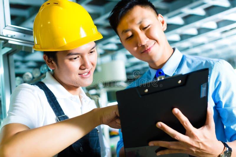 Trabalhador e gerente de produção com prancheta fotografia de stock