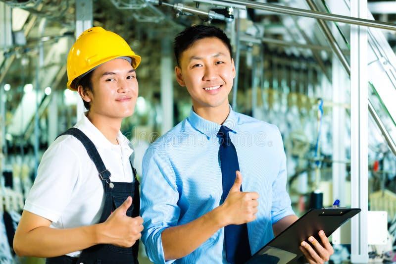 Trabalhador e gerente de produção com prancheta fotos de stock royalty free