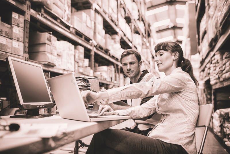 Trabalhador e gerente do armazém que olham o portátil fotos de stock