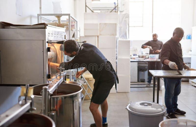 Trabalhador em feijões de cacau da repreensão da fábrica do chocolate foto de stock