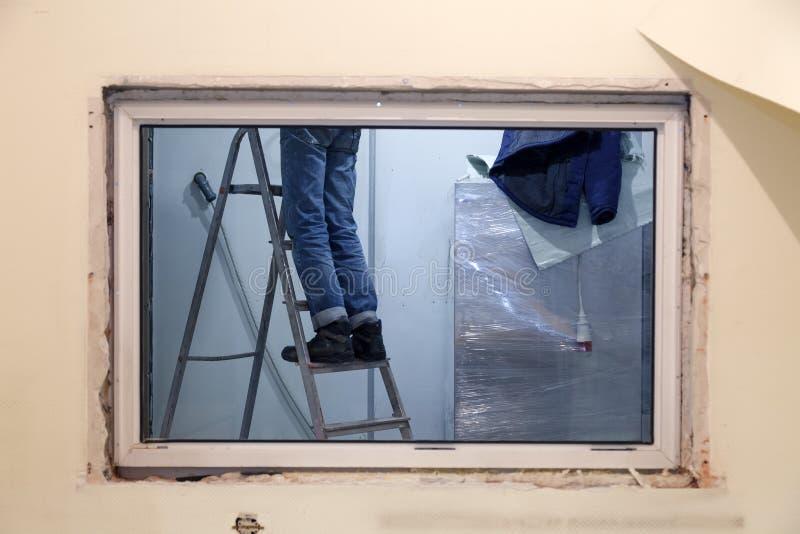 Trabalhador em suportes uniformes na escada portátil na abertura da janela Equipe da construção do conceito, trabalhos de termina imagem de stock
