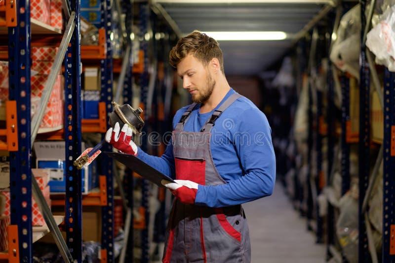 Trabalhador em um armazém das peças sobresselentes imagem de stock