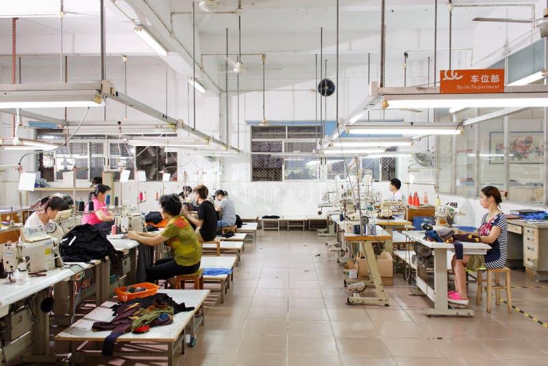 Trabalhador em uma fábrica chinesa do vestuário foto de stock