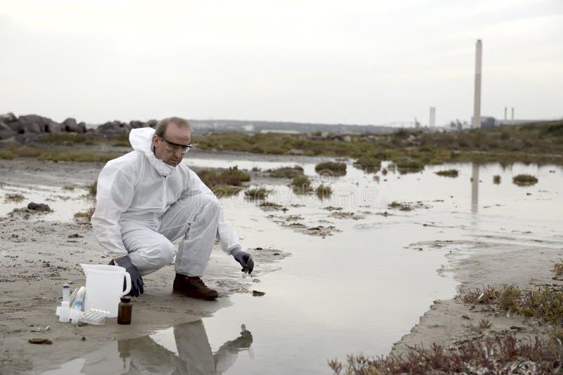 Trabalhador em uma poluição de exame do terno protetor fotografia de stock royalty free