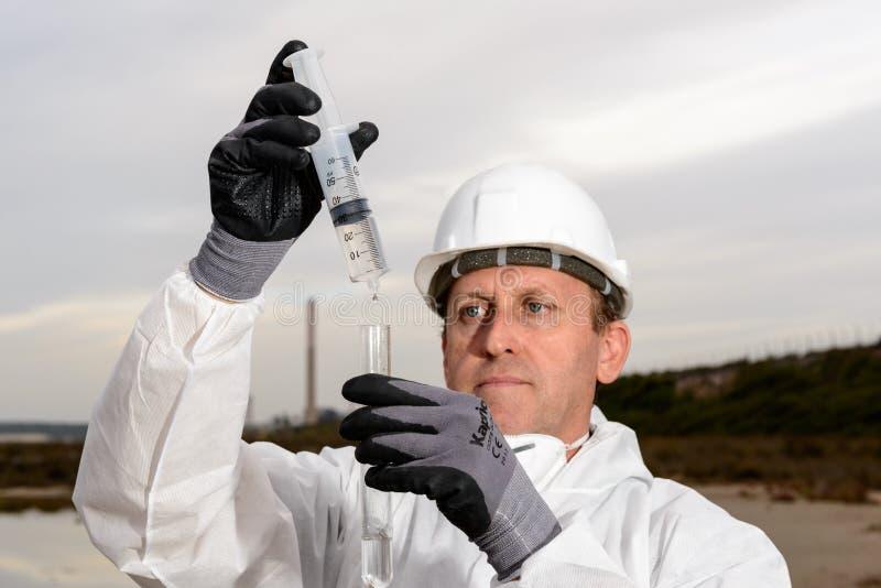 Trabalhador em uma poluição de exame do terno protetor imagens de stock royalty free