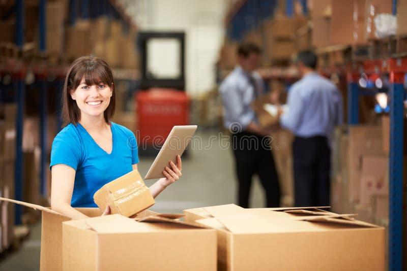 Trabalhador em umas caixas de verificação do armazém usando a tabuleta de Digitas imagens de stock royalty free