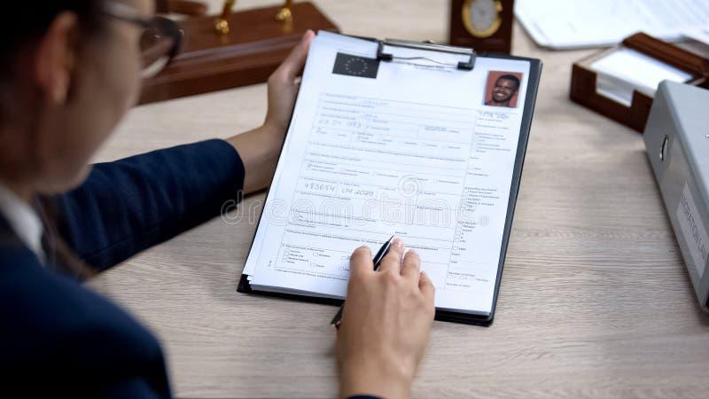 Trabalhador embaixado a verificar o pedido de visto, autorização oficial, lei de migração imagens de stock royalty free