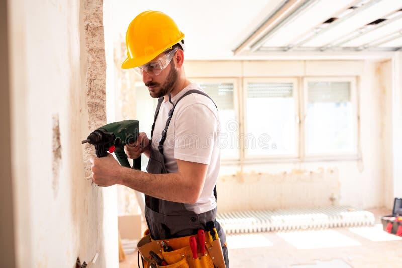 Trabalhador experiente que usa a broca de martelo fotografia de stock