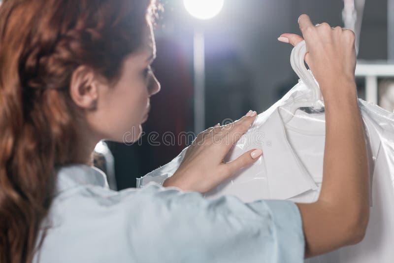 trabalhador fêmea da tinturaria que guarda a roupa limpa imagem de stock