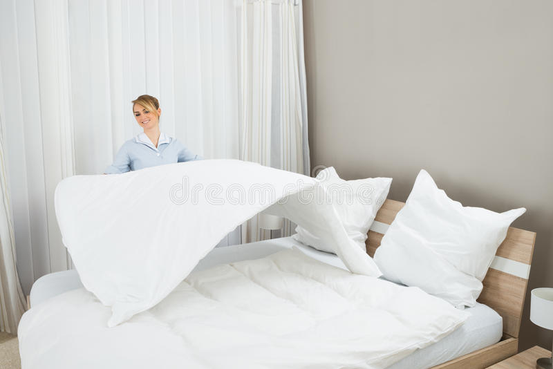 Trabalhador fêmea das tarefas domésticas que faz a cama foto de stock
