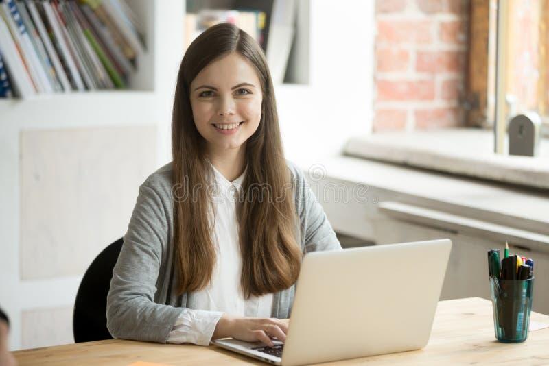 Trabalhador fêmea de sorriso que levanta ao trabalhar no portátil fotografia de stock