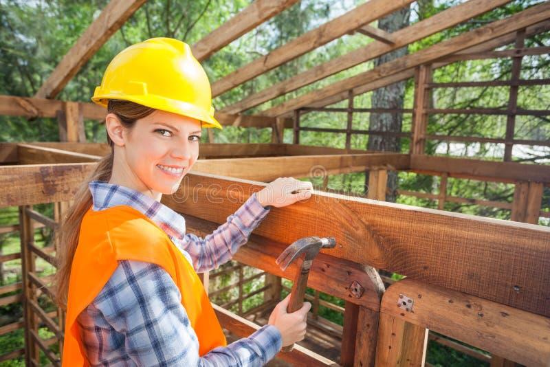 Trabalhador fêmea feliz que martela o prego no quadro de madeira imagem de stock