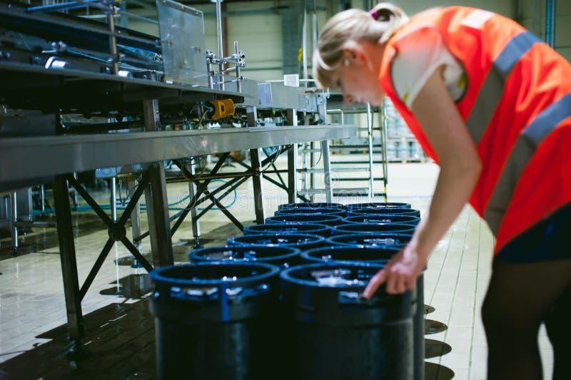 Trabalhador fêmea na fábrica da cerveja mulher do retrato na veste, estando na linha produção alimentar do fundo, controle de ges fotos de stock