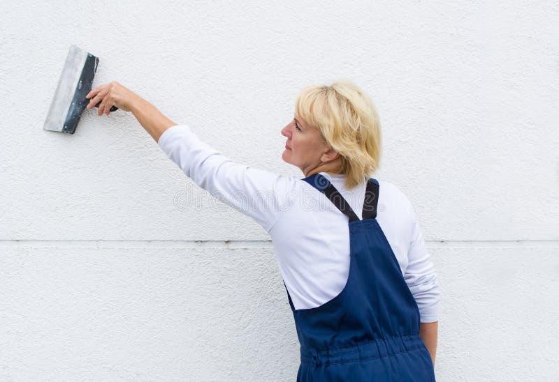 Trabalhador fêmea na renovação exterior da parede que para com espátula fotos de stock