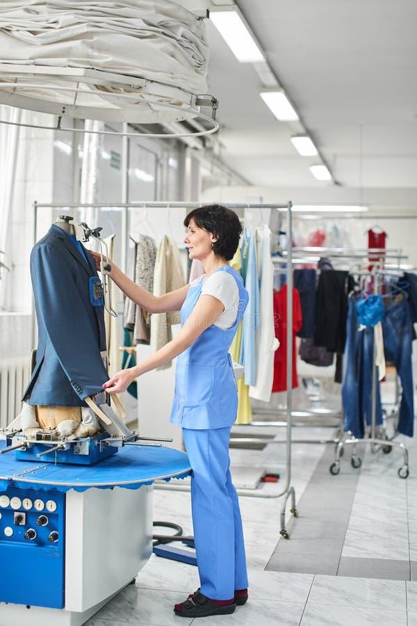 Trabalhador fêmea no serviço de lavanderia o processo de trabalho no equipamento automático universal para cozinhar, passar e lim fotografia de stock