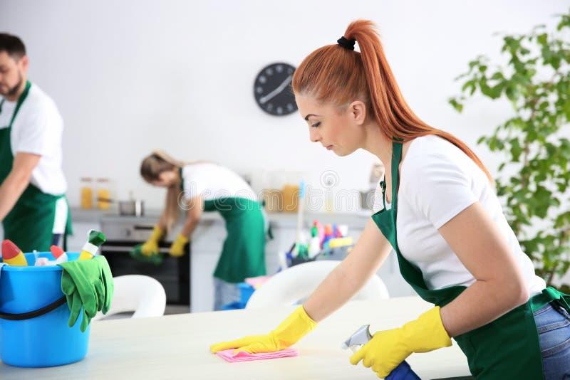 Trabalhador fêmea novo do serviço da limpeza que trabalha na cozinha imagens de stock