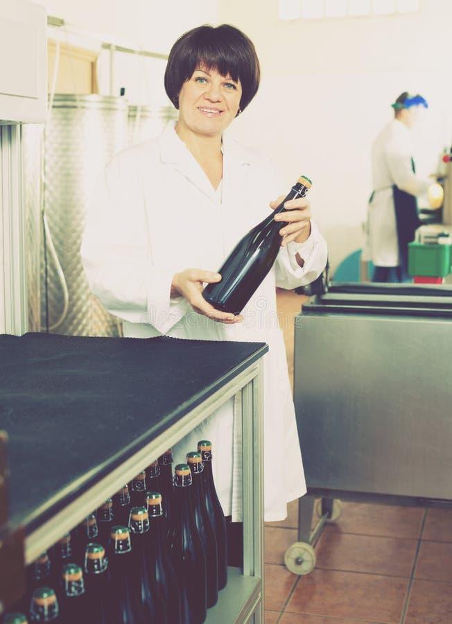 Trabalhador fêmea que classifica garrafas de vinho imagens de stock