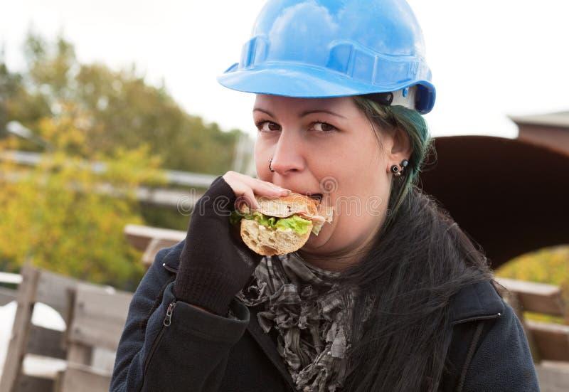 Trabalhador fêmea que come o sanduíche fotos de stock royalty free