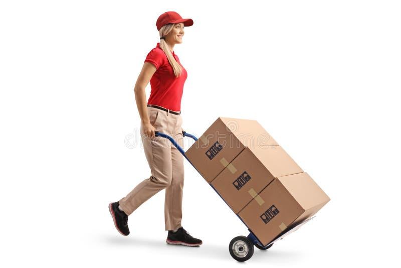 Trabalhador fêmea que empurra caixas em um caminhão de mão fotografia de stock