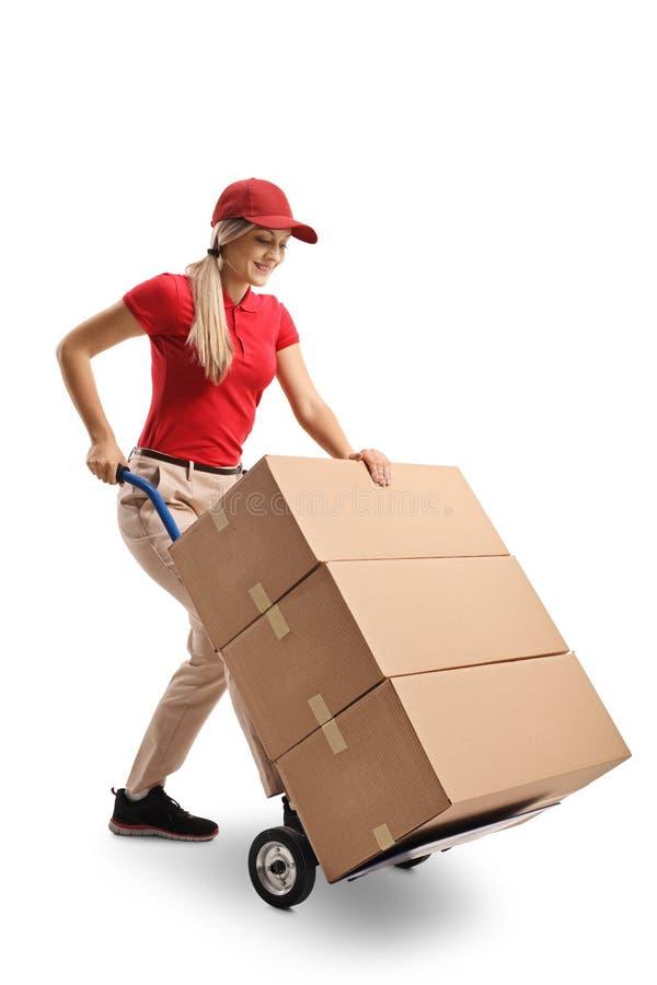 Trabalhador fêmea que empurra um caminhão de mão carregado com as caixas foto de stock